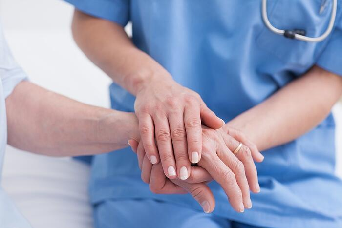 Close up of a nurse touching hand of a patient in hospital ward.jpeg