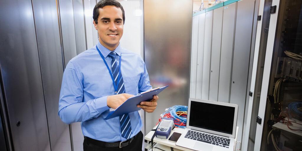 Portrait of happy technician holding clipboard in server room.jpeg